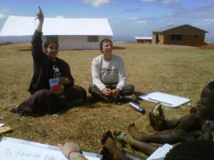 Munda and Evan teach on the grass outside our tents.